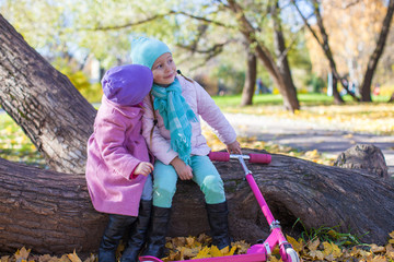 Little adorable girls with scooter in autumn park