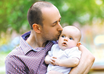 Warm, sensual photo, father kisses little baby in summer day