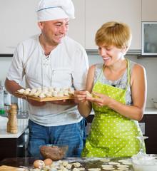 Happy couple making meat dumplings
