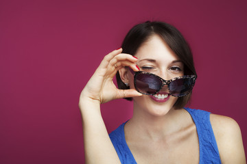 Beautiful woman on pink background with sunglasses, winking.