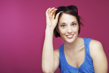 Beautiful woman on pink background with sunglasses on head.