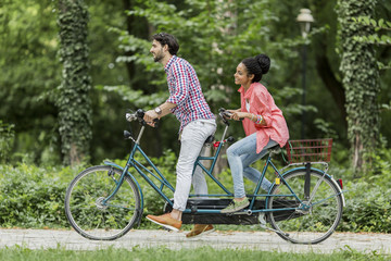 Young couple riding on the tandem bicycle
