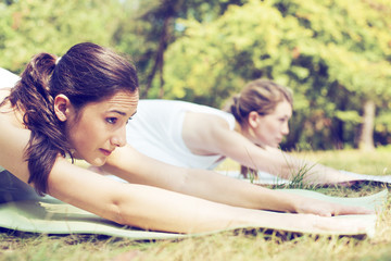 Two beautiful women doing yoga class in nature