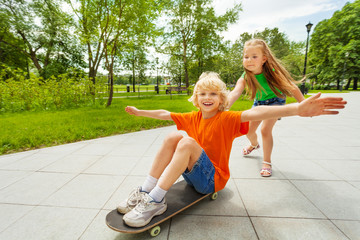 Small girl pushing happy boy on skateboard
