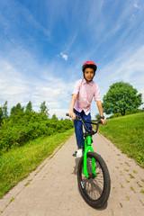 African boy in red helmet rides bright green bike