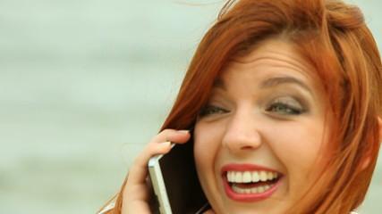 Woman talking smartphone on beach