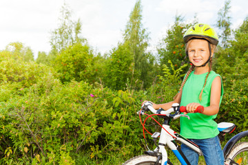Cheerful girl with braids in helmet holds bike