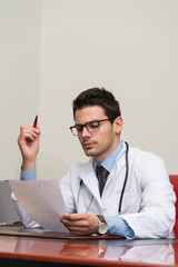Young Doctor In Office Looking At Paper