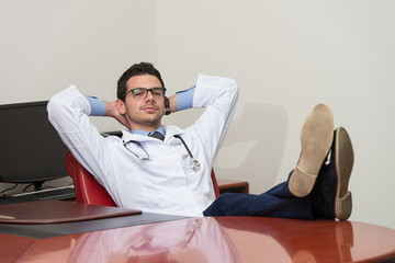 Young Doctor Relaxes Sitting In The Office