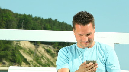 Happy man with smartphone by sea