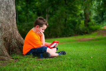 Young boy using tablet outdoors at park