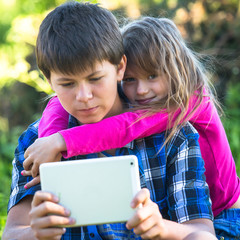 Young boy with a tablet PC and his little sister .