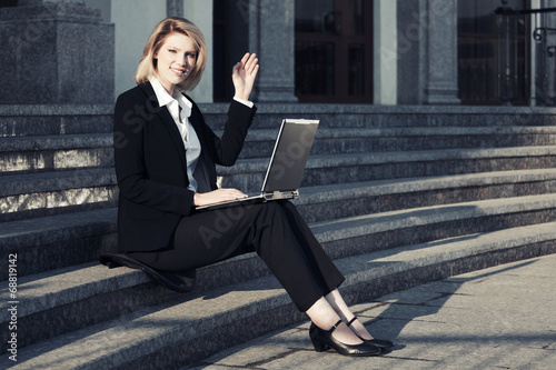 Young business woman using laptop on the steps