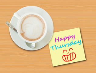 "Coffee cup on wood table with paper note ""Happy Thursday"""