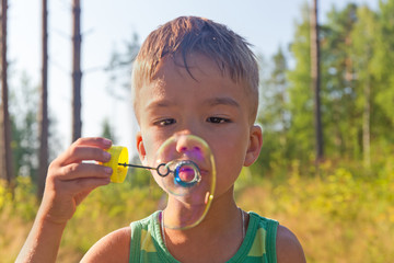 Portrait of the boy inflating soap bubbles outdoors
