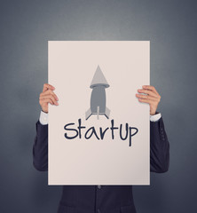 businessman hand showing poster of start up icon as concept