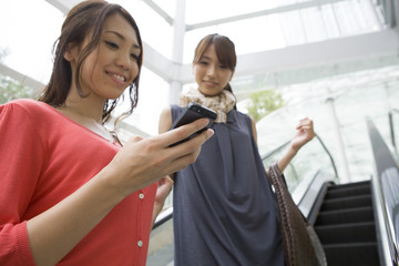 Women to confirm the mobile phone in escalator