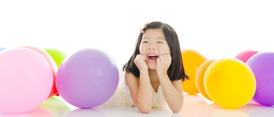 Cheerful asian kid lying on the floor with balloons