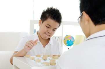 Asian boy and father playing chinese chess at home