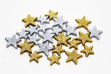 Silberne und goldene Glittersterne auf weißem Hintergrund