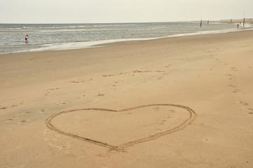 Ein Herz im weißen Sandstrand am Meer