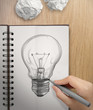hand with a pen drawing light bulb on note book as concept