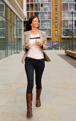 young woman walking with phone and coffee.
