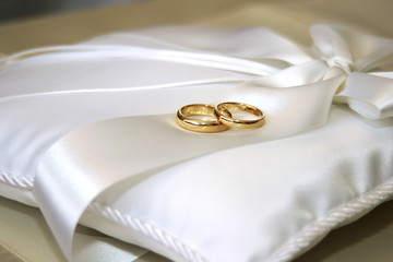 wedding rings on white pillow
