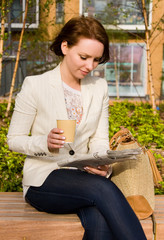 young woman reading paper and drinking coffee.