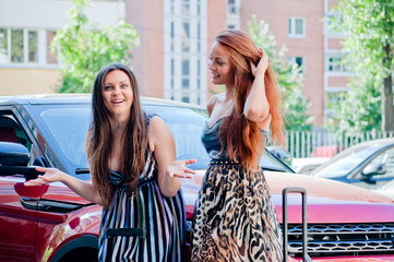 Two young and beautiful woman standing near the car