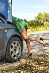 Woman standing near her broken car and looking to the engine