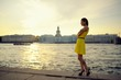 Portrait beautiful woman in yellow dress on embankment at sunset
