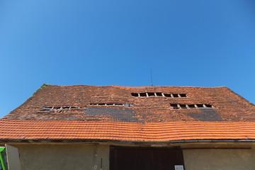 Renovierungsbedürftiges Scheunendach vor stahlblauem Himmel