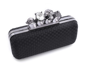 Black handbag brass knuckles and a skull on a white background