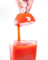 Fresh tomato juice pouring into glass