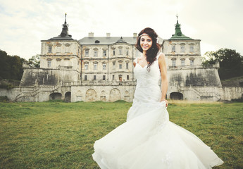 young brunette  bride against castle in west Ukraine