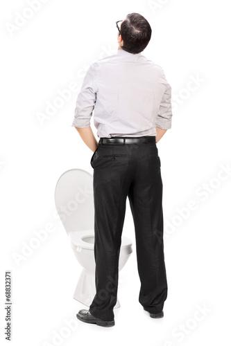 Rear view studio shot of a man taking a piss