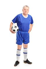 Mature man in sportswear holding a football