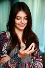Smiling beautiful woman using smartphone at home