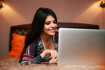 Cheerful woman lying on the bed with laptop