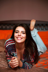 Happy attractive woman lying on the bed at home