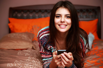 Happy beautiful woman lying on the bed and holding smartphone