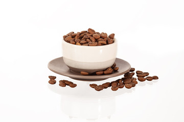 pile of coffee beans on cup isolated on white background
