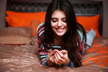 Happy beautiful woman lying on the bed with smartphone