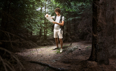 Man looking at map and planning trip or get lost in dark woods