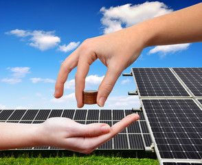 solar panels and coins in hand