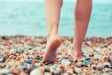 The feet of a young woman standing on the beach