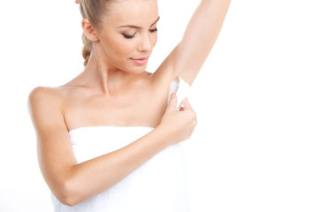 Attractive young woman shaving her armpits.