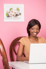 Portrait of happy young woman using laptop.