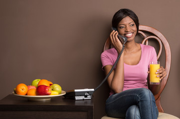 portrait of beautiful african girl using landline phone.